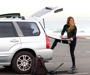 Auto, Home, Life & Business Insurance - photo of female surfer holding a surfboard while standing by her car